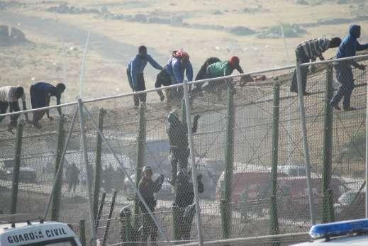 Afrikaanse migranten beklimmen de hoge hekken bij Melilla - Foto: AFP