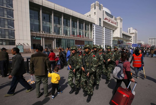 Petar Kujundzic/Reuters - Armed policemen patrol near the exit of the South Railway Station, where three people were killed and 79 wounded in Wednesday's bomb and knife attack, in Urumqi, Xinjiang province.