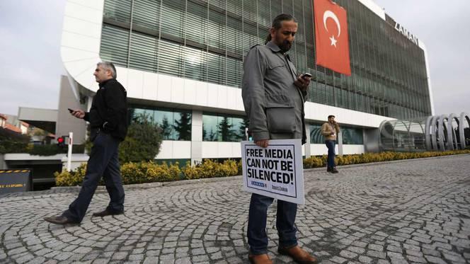 Een journalist voor het kantoor van de Turkse krant Zaman houdt een bord vast met de tekst: 'Free media cannot be silenced' © REUTERS