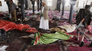 People stand amid bodies covered with blankets in a mosque after a suicide attack during the noon prayer in Sana'a, Yemen, on March 20, 2015. (photo credit: AP/Hani Mohamme