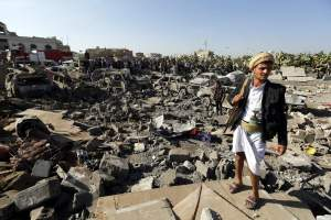 An armed member of Houthi militia keeps watch as people gather beside vehicles which were allegedly destroyed by a Saudi air strike, in Sanaa, Yemen on March 26, 2015.