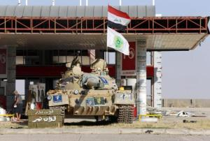 A tank belonging to the Shi'ite Badr Brigade militia takes position in front of a gas station in Suleiman Beg, northern Iraq in this September 9, 2014 file photo. REUTERS/Ahmed Jadallah/Files