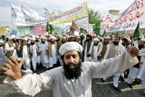 Islamabad, PAKISTAN:  An activist of Pakistani Islamic party Jamaat-e-Ahle Sunnat shouts slogans as others carry banners during an anti-cartoon protest rally in Islamabad, 13 March 2006.  Some 1,000 protesters marched on the streets to protest against the controversial publication of cartoons of the Prophet Mohammed. Twelve cartoons depicting the Prophet Mohammed were first published in Denmark's Jyllands-Posten newspaper in September 2005 and have since been reprinted elsewhere, igniting demonstrations throughout much of the Islamic world.             AFP PHOTO/Aamir QURESHI  (Photo credit should read AAMIR QURESHI/AFP/Getty Images)