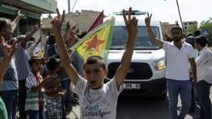 © afp. Archieffoto van inwoners van Kobani die de overleden militair Keith Broomfield gedenken. De Amerikaan stierf tijdens gevechten tegen IS.
